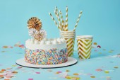 Delicious cake, plactic cups and drinking straws on blue background with confetti