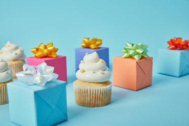 Delicious cupcakes and colorful gifts on blue background stock vector