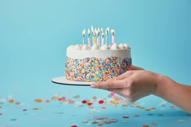 Partial view of woman holding birthday cake with candles on blue background with confetti stock vector