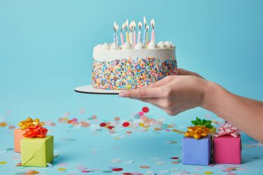 Cropped view of woman holding birthday cake with candles on blue background with confetti and gifts