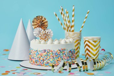 Cake, party hats, plactic cups, golden paper streamer  and drinking straws on blue background with confetti
