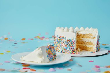 Slice of cake with cut cake on blue background with confetti