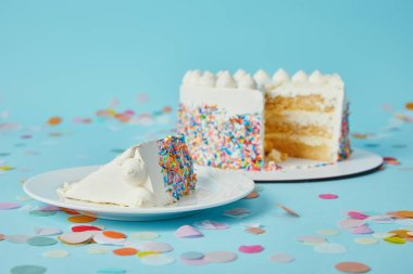 Piece of cake with cut cake on blue background with confetti