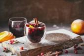 domácí svařené víno s brusinkami, pomerančem a skořicí hole na dřevěný stojan v kuchyni