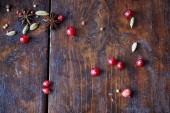 pohled shora rozptýlené brusinky, karafiát a pepř na dřevěný stůl v kuchyni