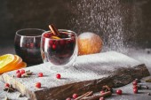 Fotografie tasty homemade mulled wine with cranberries and falling powdered sugar in kitchen