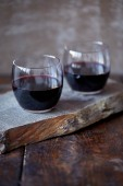 Fotografie Two glasses of homemade red wine on wooden stand in kitchen