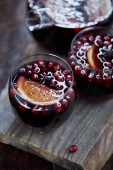 Fotografie high angle view of glasses of homemade mulled wine with cranberries and oranges on wooden stand in kitchen