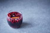 sklenici chutné domácí svařené víno s brusinkami a oranžové na šedou desku v kuchyni