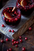Fotografie high angle view of homemade mulled wine with cranberries and cinnamon stick on board in kitchen