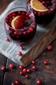 Photo high angle view of glasses of homemade mulled wine with cranberries on wooden stand in kitchen