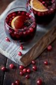 pohled z vysokého úhlu sklenic domácí svařené víno s brusinkami na dřevěný stojan v kuchyni