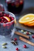 Detail domácí svařené víno s brusinkami a pomeranče na stole v kuchyni