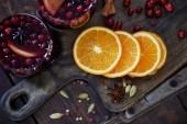 pohled shora na domácí svařené víno s brusinkami a pomeranče na prkénku v kuchyni