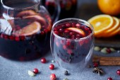 Fotografie close up of homemade mulled wine with cranberries and oranges on table in kitchen