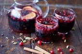 Fotografie homemade mulled wine with cranberries in glasses and teapot on wooden table in kitchen