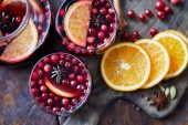 Fotografie elevated view of homemade mulled wine with cranberries and oranges on table in kitchen