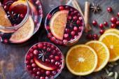 pohled shora na domácí svařené víno s brusinkami a pomeranče na stole v kuchyni