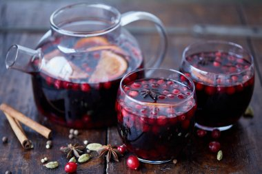 homemade mulled wine with cranberries in glasses and teapot on table in kitchen