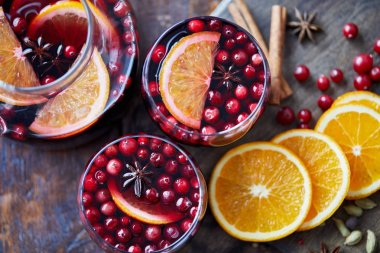 top view of homemade mulled wine with cranberries and oranges on table in kitchen