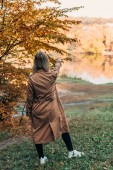 Fotografie Back view of woman standing in coat and pointing at lake in autumn forest
