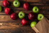 top view of ripe red and green apples with paper bag on wooden table