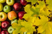 Fotografie top view of ripe multicolored apples and yellow maple leaves on wooden table