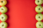 Fotografie vertical frame of ripe green apples on red background