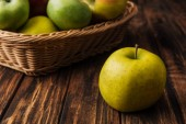 Fotografie golden delicious apple with fruit wicker basket at background