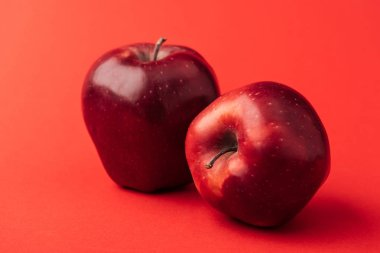 ripe large apples on red background