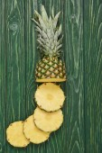Fotografia vista superiore di affettato cerchi di gustosi ananas sulla tavola di legno verde