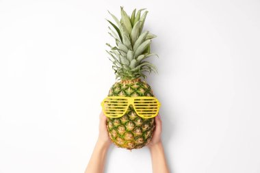 cropped view of woman holding pineapple in sunglasses on white background
