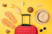 felülnézet, szalmakalap, napszemüveg, kókusz, flip papucs, utazik táska és a tengeri kagylókból a sárga háttér