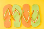 top view of colorful flip flops on yellow background