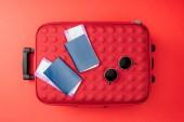 pohled shora cestovní tašku, pasy, letenky a sluneční brýle na červeném pozadí