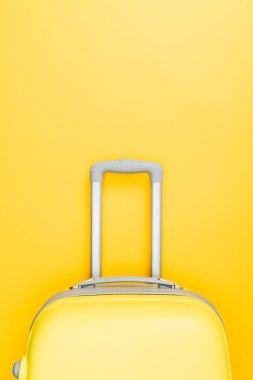 top view of travel bag with handle on yellow background
