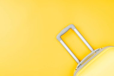 top view of baggage with handle on yellow background