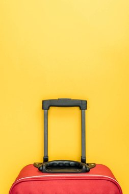 top view of red baggage with handle on yellow background