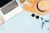 vista superiore dellaereo giocattolo, computer portatile con lo schermo in bianco, cuffie, occhiali da sole, conchiglie, flip flop, modello dellaereo e cappello di paglia su priorità bassa blu