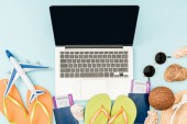 Fotografie top view of laptop with blank screen, flip flops, passports with air tickets, sunglasses, seashells, straw hat and plane toy on blue background