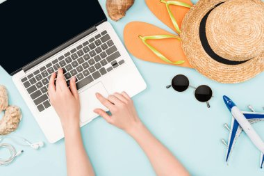 cropped view of woman using laptop near earphones, sunglasses, seashells, flip flops, toy plane and straw hat on blue background