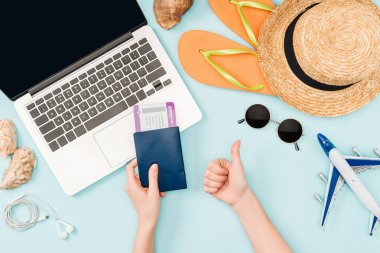 cropped view of woman holding passports and air tickets while doing thumb up gesture near laptop, earphones, sunglasses, seashells, flip flops, toy plane and straw hat on blue background
