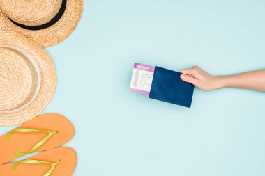 Cropped view of woman holding air ticket and passport near flip flops and straw hats on blue background stock vector