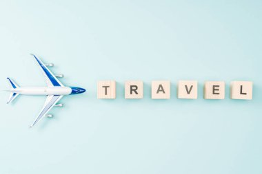 top view of toy plane and wooden cubes with travel lettering on blue background