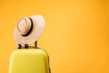 travel bag, straw hat and sunglasses isolated on yellow