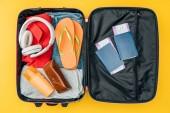 vista superiore di paglia cuffie, passaporti e biglietti aerei in borsa da viaggio isolato su colore giallo