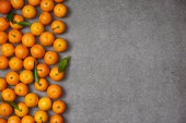 Fotografie top view of ripe organic clementines with green leaves on grey table