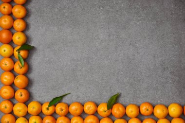 top view of ripe organic tangerines with green leaves on grey table