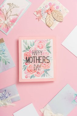 Happy mothers day greeting card with flowers, and various mothers day postcards arranged around on pink background stock vector