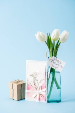 Happy mothers day greeting card, bouquet of white tulips with paper label, and gift box on blue background stock vector